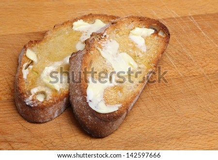 Two slices of toasted artisan bread with melting butter.