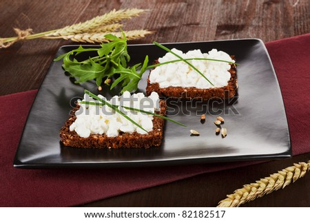 Two slices on black whole wheat bread with cottage cheese and fresh chive and arugula on black plate. Healthy eating background. - stock photo