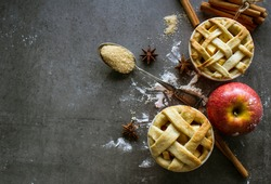 Two small apple pies with lattice.  Grey background with copy space.