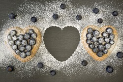 Two small blue heart shaped cake cakes lie on a slate plate. They are sprinkled with powdered sugar and garnished with blueberries. A cake is missing