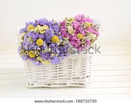 Two small bouquets of dried flowers put into a white basket.