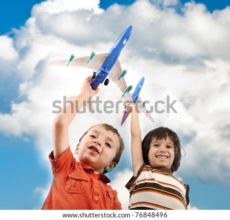 Two small boys with airplains in hands, idea for traveling around the World