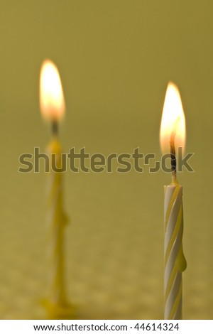 two small burning candles on yellow background, shallow depth of field