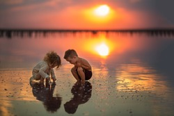 Two small children playing on the seashore during sunset. Reflection in water