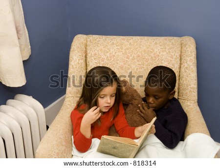 Two small children reading together in a big chair.  Diversity.