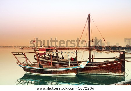 Two small fishing dhows of different types tied up in Doha harbour at dawn. The main post office and high-rise buildings of the New District are visible behind the row of boats opposite.