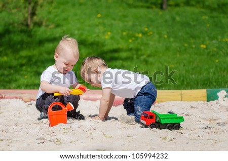 two small friends playing toys in sand