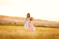 two small girls chasing soap bubbles on the sloping wheat field at sunset in village