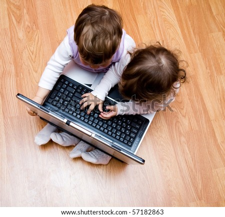 Two small girls-girl-friends together play with the laptop