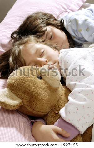two small girls sleeping and embracing a felt bear