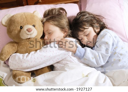 two small girls sleeping with a plush bear