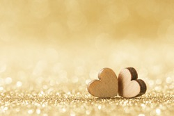 Two small handmade wooden hearts on bright golden lights bokeh background Valentines day card