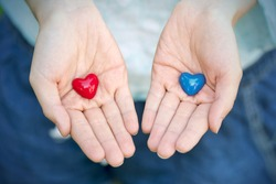 Two small red and blue heart on female hands