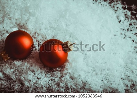 Two Small red Christmas balls. Two Red mate Christmas balls in snow and blur photo studio background table #1052363546