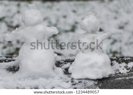 Two small rough snowmen with snow is on the black and white photo
