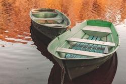Two small rowboats are anchored at coast of a still lake