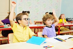 two small school children-a boy with curly hair and a boy in a yellow shirt and glasses-smile and hold up their hand against the background of the classroom and a group of classmates. Back to school