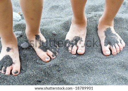 Two small sets of feet in black sand on the beach.