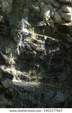 Two small Waterfalls flowing over the rock, and which flows into the lake #1401277667