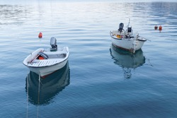 Two small white fishing boat in calm water in the first morning light