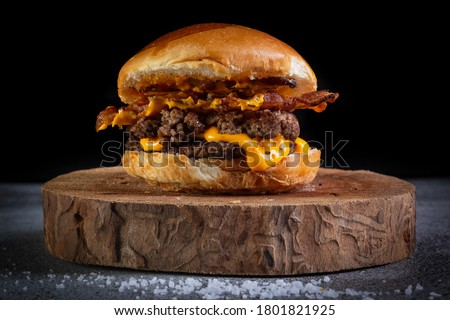 Photo of  Two smash burgers with cheddar cheese, bacon and garlic sauce. Rustic craft burger.