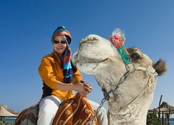 Two smiles. On a white camel sits a smiling woman in a yellow jacket and a bright turban. The camel turned its head in the direction of the rider and also smiles.