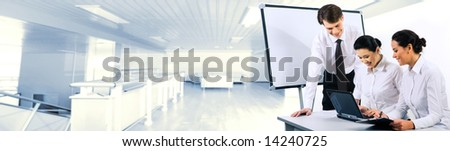 Two smiling business ladies sitting at table and looking at laptop monitor while their partner standing near by