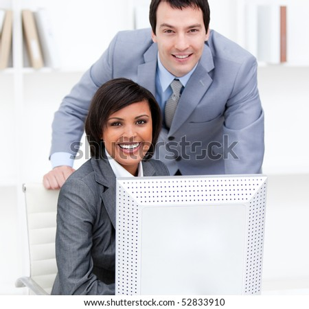 Two smiling business partners working at a computer in the office - stock photo