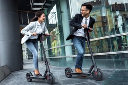 Two smiling business people driving electric scooter in front of modern business building going on work.