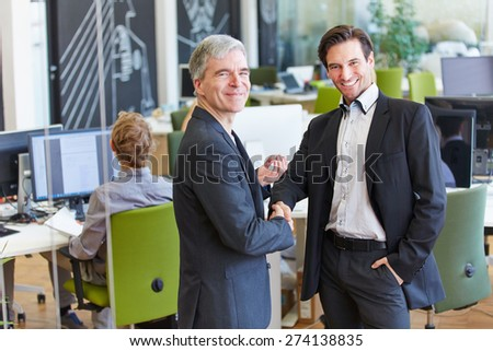 Two smiling business people giving handshake in the office