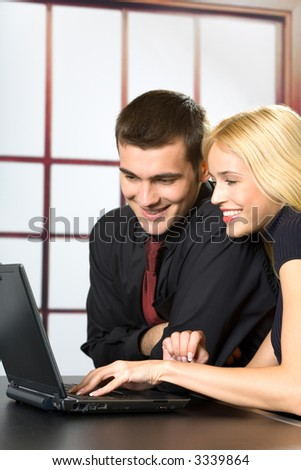 Two smiling business people on laptop, working, chatting, playing or searching in web