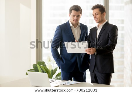 Two smiling businessmen talking about eligible investment, manager presenting financial report showing good work results to satisfied boss, pointing on paper, offering deal, discussing new project