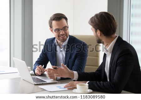 Two smiling businessmen working at laptop in office discussing ideas, happy managers or workers talk analyzing company financial statistics, considering new projects or startups. Cooperation concept