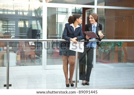 two smiling businesswomen chatting in the office corridor