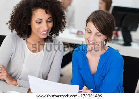 Two smiling businesswomen working on a document as they sit close together at a desk in the office, one is African American #176981489