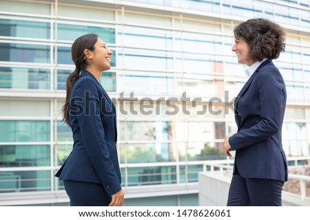 Two smiling colleagues standing on street. Cheerful young confident employees wearing formal suits looking at each other. Business confidence concept
