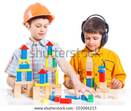 Two smiling cute boys is building a toy block. Isolated on white background