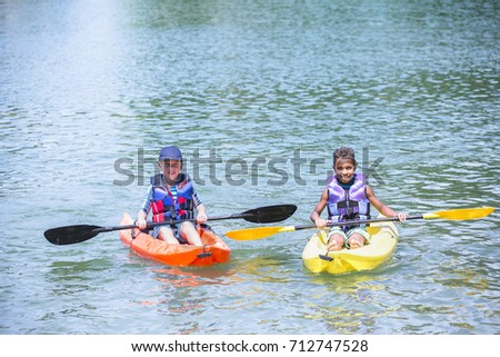 Two smiling cute diverse boys kayaking together on the lake. Having fun in the summertim #712747528