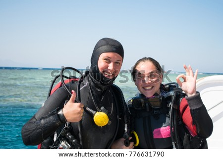 two smiling divers in wet suits show ok on the background of the sea. two happy girls on the background of azure sea in wetsuits and in diving equipments   #776631790