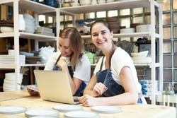 Two smiling female entrepreneur with laptop in artisan workroom. Waist up portrait of cheerful smiling woman artisan posing in pottery studio and looking at camera