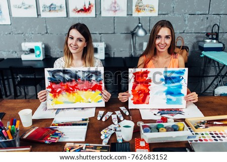 Two smiling female illustrators working in their workshop holding paper sheets with flags of France and Germany drawn with watercolor technique #762683152