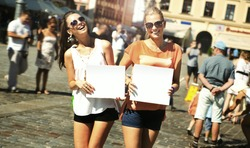 Two smiling girls holding empty board