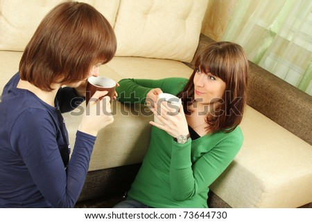 Two smiling girls in the room drinking tea, chatting and playing