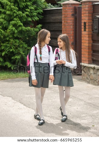 Two smiling girls in uniform walking to school and chatting #665965255