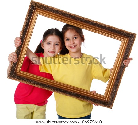 Two smiling girls looking through a vintage picture frame, isolated on white