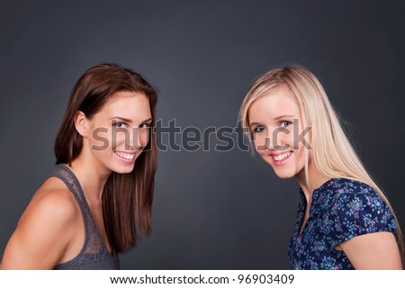 Two smiling girls on gray background