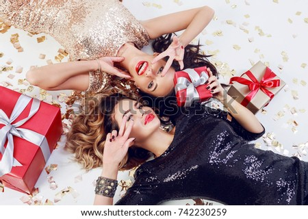 Two smiling gorgeous  women  in trendy sequin dress lying on white floor with shining golden confetti and red gift boxes . Celebrating new year or birthday party. Showing peace.