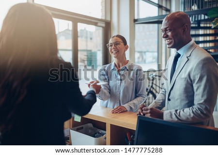 Two smiling guests giving their reservation details to a concierge while checking in together at the reception counter of a hotel Stock photo ©