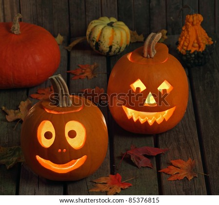 Two smiling halloween jack-o-lanterns on a wood floor