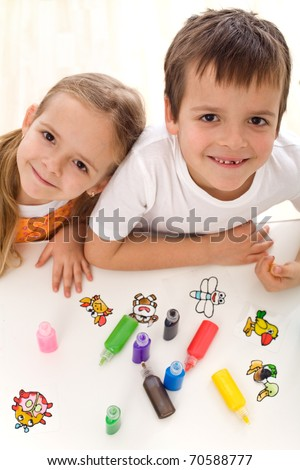 Two smiling happy kids painting with lots of colors in small bottles - top view